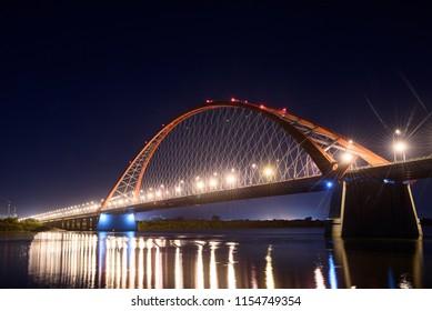 Bridge over the river Ob night. The lights of the bridge glow in the night sky. in the sky are visible star tracks.