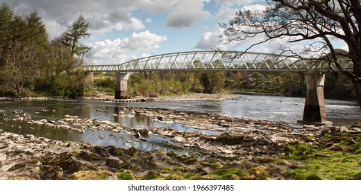 Bridge over river with rocks and blue sky with clouds