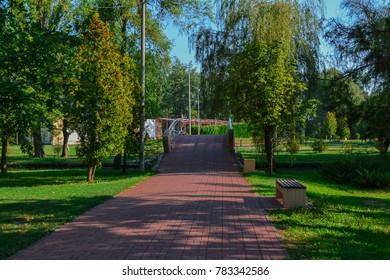 Bridge over river in sunny park in summer, Pitesti, Romania