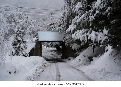 Bridge over a snow path with tire tracks and under chair lifts of Nevados de Chillán Ski Resort, in Chile. August 06, 2019.