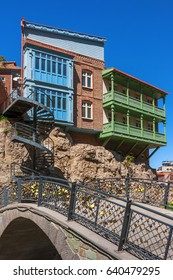 Bridge with padlocks, a spiral staircase and residential houses on a rock in Tbilisi