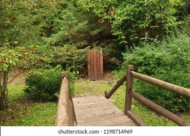 Bridge in a park leading to a wooden door. Summer season.
