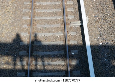 Bridge and people shadows over a railway tracks