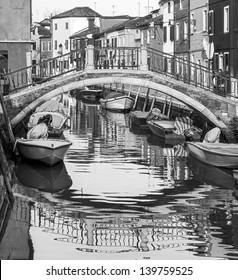 The bridge and the picturesque houses on the shore of a narrow channel - Burano, Venice, Italy (black and white)