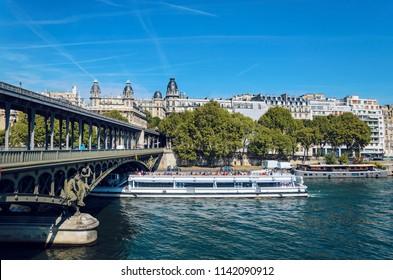 Bridge Pont Bir Hakeim and tourist boat tour on Seine river under dramatic sky