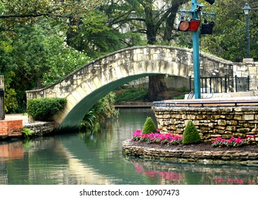 Bridge is reflected in the still waters of river on the San Antonio River Walk.  Flowers in pink bloom along river's edge.