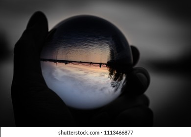 Bridge and Reflection in Crystal Ball during sunset. hand holding chrystal abll