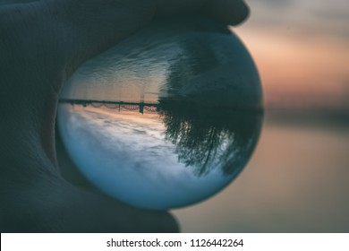 Bridge and Reflection in Crystal Ball during sunset. hand holding chrystal abll - vintage retro look