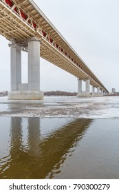Bridge in reflection in a frozen river at winter