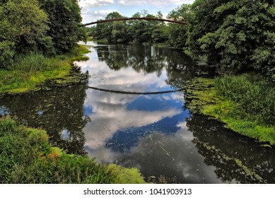 Bridge reflection on the river looking like an eye. Rushes and duckweed on the water stream in full bloom. Spring or summer season. Clouds visible in the water, thick green forest. Beautiful landscape