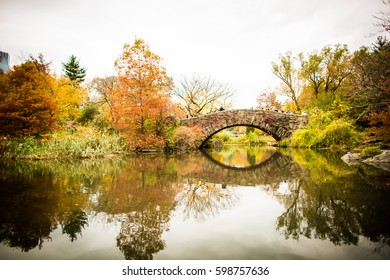 Bridge with a reflection in the water during autumn in Central Park, New York City.