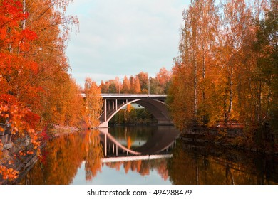 Bridge with reflections in the water. Image has fantasy colored woods.