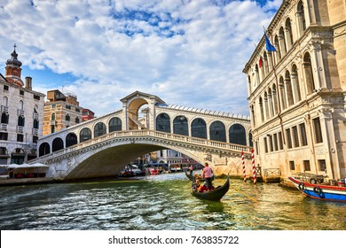 Bridge Rialto on Grand canal famous landmark panoramic view Venice Italy with blue sky white cloud and gondola boat water