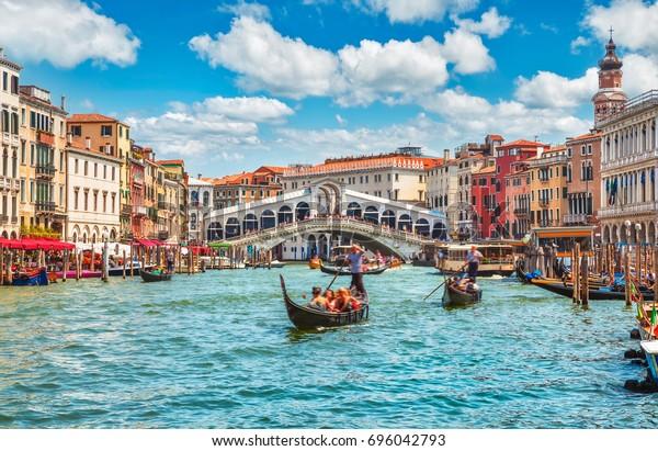 Brücke Rialto auf dem Grand Kanal berühmte Wahrzeichen Panorama Blick Venedig Italien mit blauem Himmel weißen Wolke und Gondelboot Wasser.