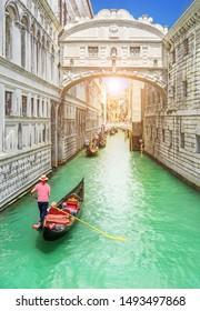 Bridge of Sighs (Ponte dei Sospiri) and row of gondolas with gondoliers and Rio de Palazzo o de Canonica Canal from Riva degli Schiavoni in Venice, Italy. Ponte de la Canonica is visible in background