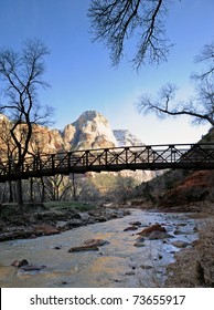 A bridge in silhouette crosses the Virgin River in Zion National Park, Utah as mountains still capped with snow rise in the bright sun in the distance.