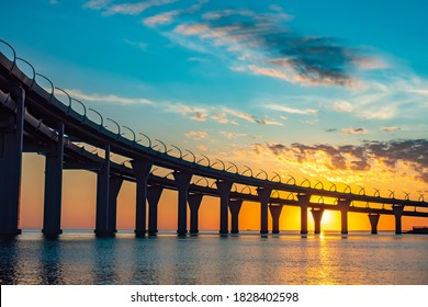Bridge silhouette on background of sunset. Cityscape with sunset. Silhouette of bridge over evening bay. Bridgework silhouette on a summer evening. Double car bridge over bay. Bottom view - Shutterstock ID 1828402598