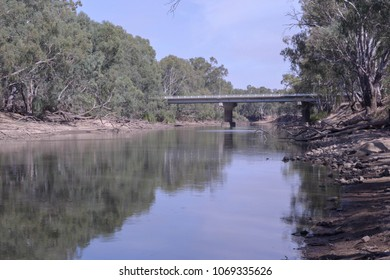 a bridge spanning across the Murrumbidgee river thats half full of water on a sunny day but with clouds in the sky