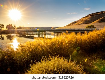 a bridge spanning across the snake river in glenns ferry idaho during sunrise or sunset with a slow shutter speed to motion blur grasses and water with a lens flare
