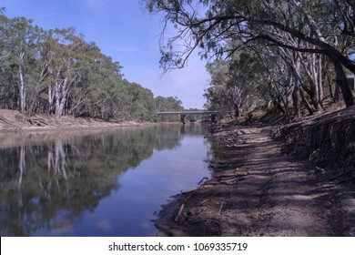 a bridge spanning the banks of the Murrumbidgee river with trees along the banks on a sunny day and clouds in the sky