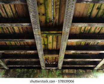 A Bridge Under view of Steel Beams and Wooden Beams Supporting Railway Tracks Above
