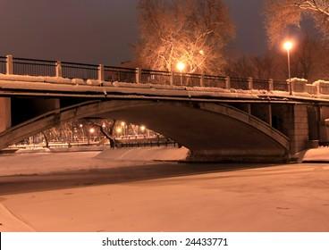 Bridge in the winter park in the night
