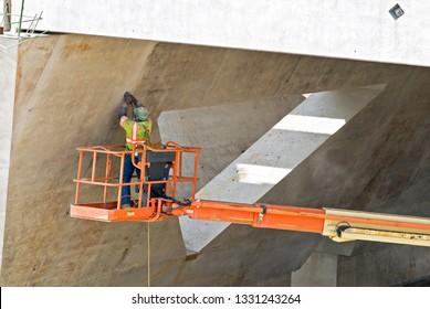 Bridge Worker Sanding Bridge Seams