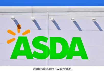 Bridgend, County Borough of Bridgend/Wales UK-4/18/2018: Close up of Asda store sign on side of building. Blue sky above. Shadows caused by sign lighting lamps.