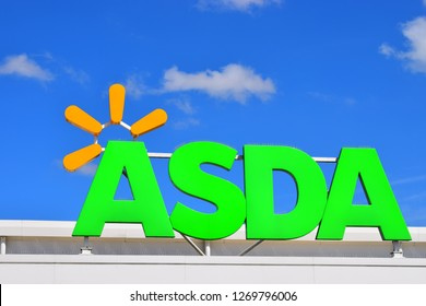Bridgend, County Borough of Bridgend/Wales UK-4/18/2018: Close up of the distinctive Asda store sign above the entrance to the Bridgend Superstore. Blue sky with white clouds behind.