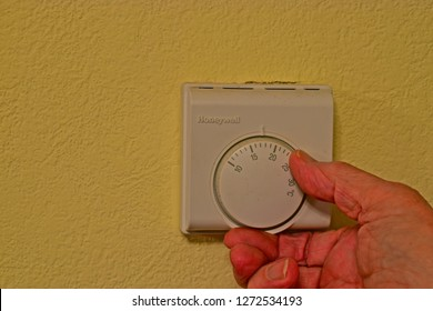 Bridgend, Bridgend County Borough / Wales UK - 1/21/2018:Turning down thermostat to save money/ turning it up to keep warm! Close-up of hand adjusting wall thermostat for central heating system.