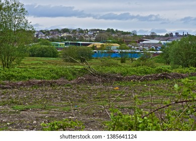 Bridgend, Bridgend County Borough / Wales UK - 4/28/2019: A section of scrubland on a brownfield site close to existing housing developments and industrial buildings. Potential new building site.