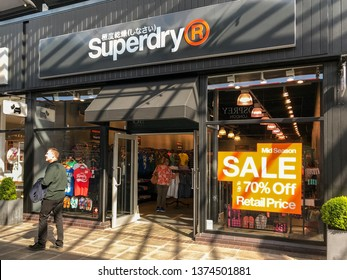 BRIDGEND, WALES - MARCH 2019: Shopper walking past an a branch of Superdry in the McArthur Glen outlet shopping mall in Bridgend.