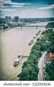 Bridges over the Danube river in Bratislava city, Slovak republic. Docks scene. Old bridge and Apollo bridge. Ship transportation. Travel destination. Analog photo filter with scratches.