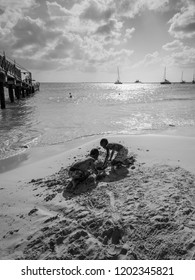 Bridgetown, Barbados - December 18, 2016: The boys play with sand on the Brownes beach at sunny day in Carlisle bay, Bridgetown, Barbados, West Indies, Caribbean. Black and white photography.