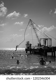 Bridgetown, Barbados - December 18, 2016: Boy bungee jumping over water on the Brownes beach at sunny day in Carlisle bay, Bridgetown, Barbados, West Indies, Caribbean. Black and white photography.