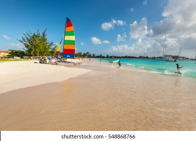 Bridgetown, Barbados - December 18, 2016: Brownes beach at ocean coast with people and colorful sail on a yacht at sunny day in Bridgetown, Barbados.