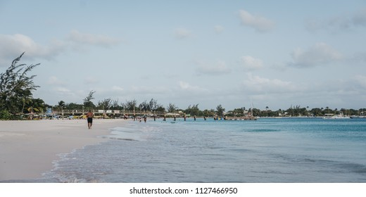 BRIDGETOWN, BARBADOS - JUNE 26, 2018: Carlisle Bay beach in Bridgetown, Barbados, unidentified man running along the water. It is a popular tourist destination and lies in the heart of a UNESCO site.