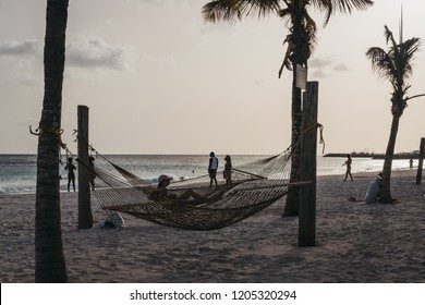 Bridgetown, Barbados - June 26, 2018: People relaxing in Carlisle Bay beach, Bridgetown, Barbados, at dusk. Carlisle Bay is a popular tourist destination located within UNESCO World Heritage Site.