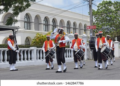 Bridgetown, Saint Michael, Barbados. March 22, 2018. Changing of the guard outside historic garrison. Sargeant major gives salute with drummers in background. Arches of former British garrison visible