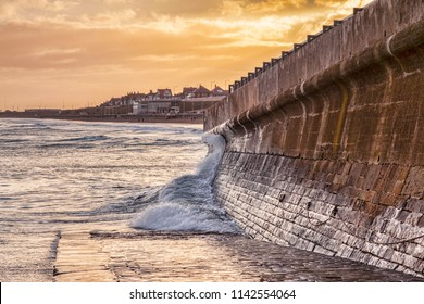 Bridlington, East Yorkshire, on a winter afternoon. A wave splashes against the sea wall.