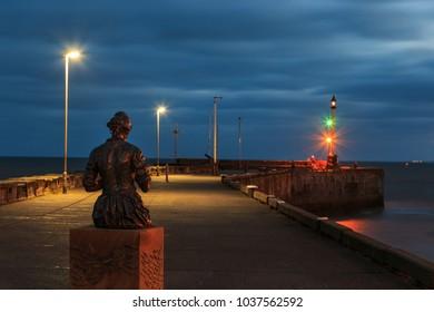 BRIDLINGTON, ENGLAND - FEBRUARY 24: Bridlington's 'Gansey Girl' statue by Steve Carvill, at night. In Bridlington, England. On 24th February 2018.