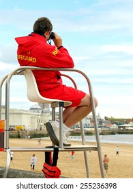 BRIDLINGTON, YORKSHIRE, UK. JULY 18, 2009. A lifeguard sits in his chair looking for any trouble on the beach or in the sea at Bridlington, Yorkshire, UK.