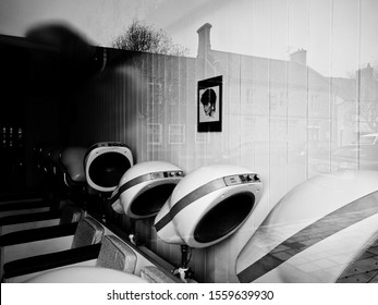 BRIDPORT, DORSET, UK - November 14 2019: Black and white photo of interior of a ladies hairdressers, with old style original fittings and dryers. Focus on detail. Framed photo of a woman on the wall.