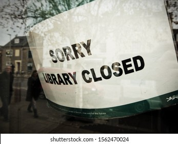 BRIDPORT, DORSET, UK - November 17 2019: Notice on Library door says 'SORRY LIBRARY CLOSED', focus on foreground detail, reflection in the window of people passing by, looking at the sign.