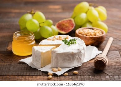 Brie or Camembert cheese with grapes, honey, figs on wooden background. Closeup view