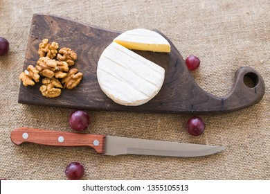Brie or camembert cheese with nuts and grapes on a wooden board top view
