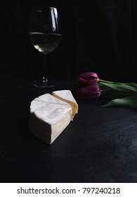 Brie cheese cuts with white wine and purple tulips. Black stone background. Delicious gourmet French background. Side view