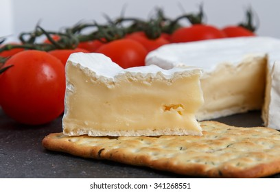 Brie soft cheese with crackers and  tomato  on a grey slate board.  Selective Focus