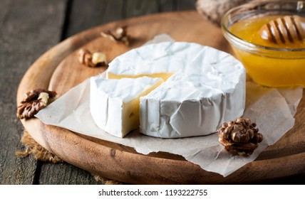 Brie type of cheese. Camembert cheese. Fresh Brie cheese and a slice on a wooden board with nuts, honey and leaves. Italian, French cheese.