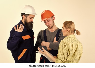 Brigade of workers, builders in helmets, repairers, lady arguing, discussing contract, white background. Misunderstanding concept. Woman amend plan of repair. Supervisor not satisfied with renovation.